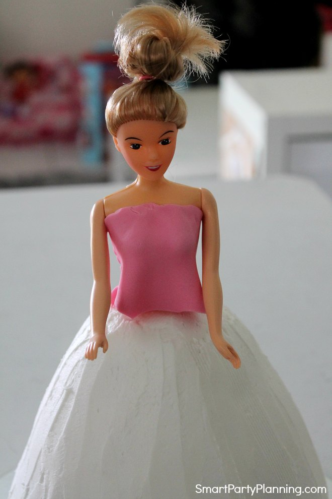 Sit the doll in the top of the cake