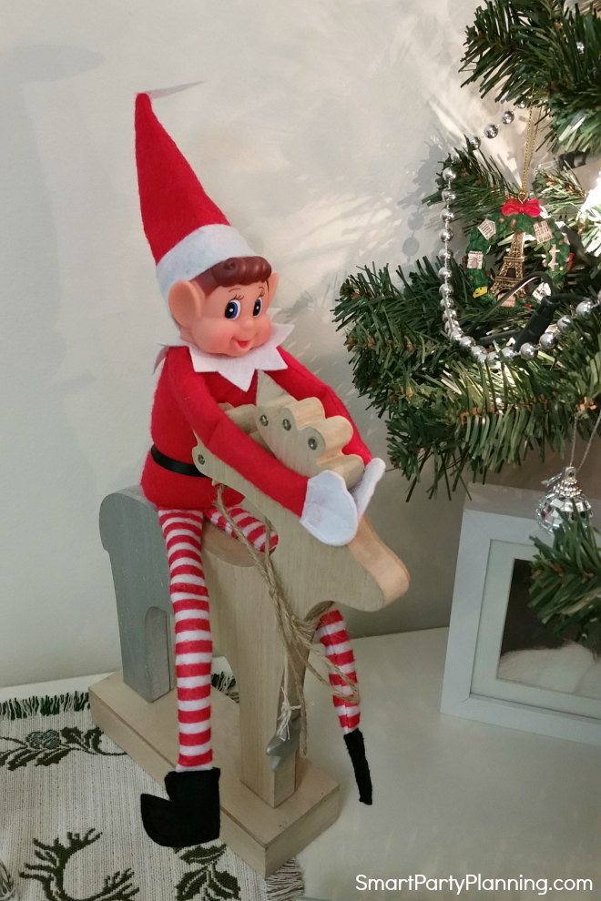 Elf plays with Christmas decorations