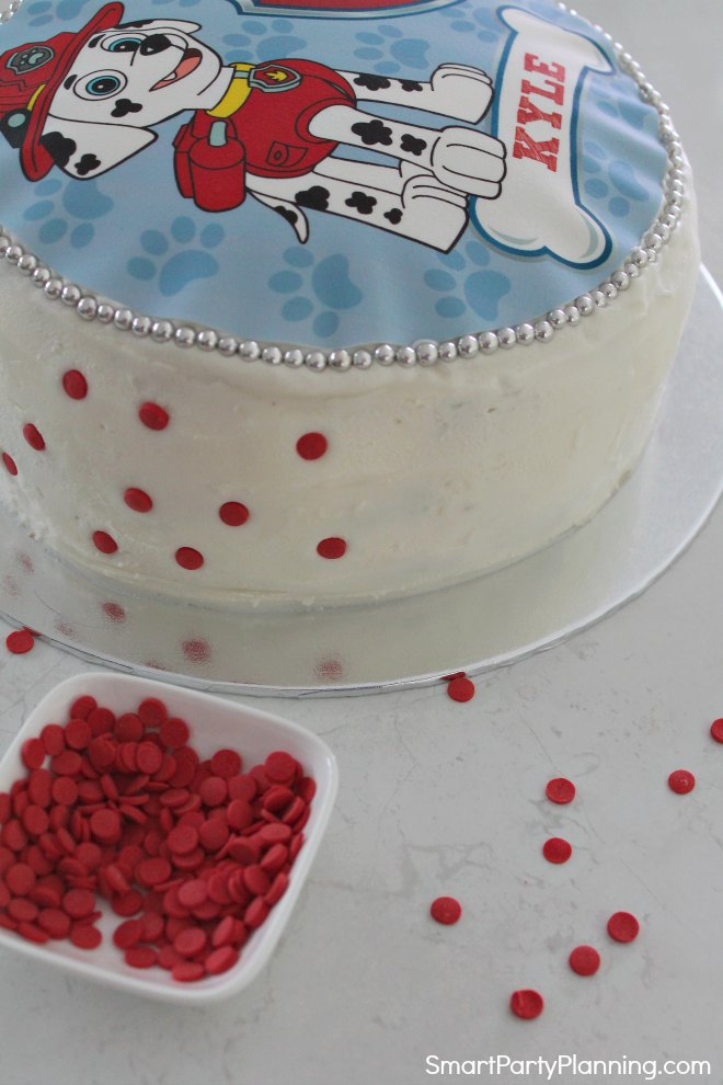 Add red sugar drops to the side of the Paw Patrol cake
